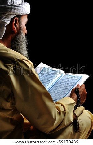 Muslim reading Koran - stock photo
