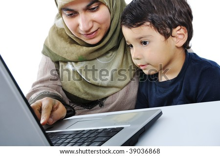 Muslim woman and her son on laptop - stock photo