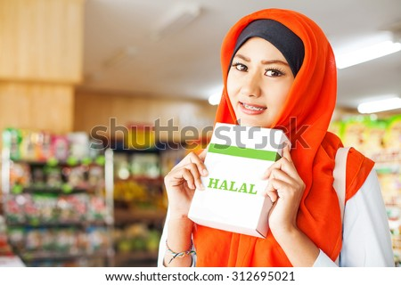 muslim woman buying halal food in a supermarket - stock photo