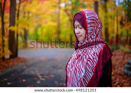 Muslim woman in Canada during autumn with colorful maple leaf as background