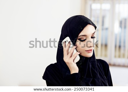 Muslim woman in hijab talking on a cell phone while working in the office - stock photo