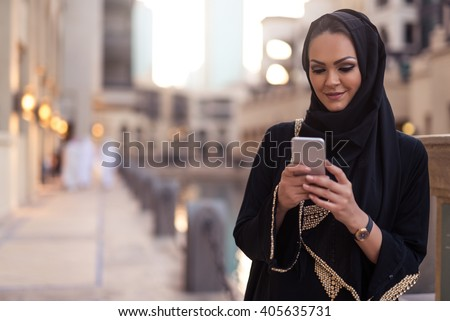 Muslim woman messaging on a mobile phone in the city. - stock photo