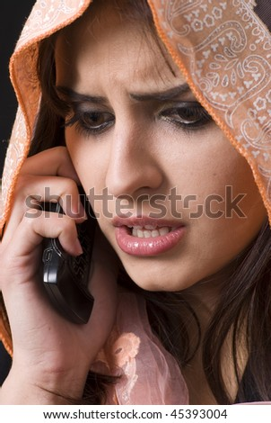 Muslim woman on the phone receiving bad news - stock photo