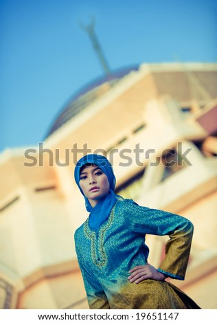 muslim woman posing in front mosque - stock photo
