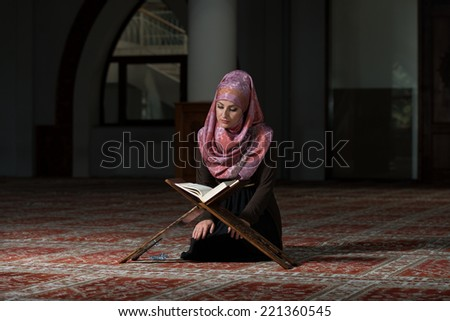 Muslim Woman Reading Holy Islamic Book Koran - stock photo