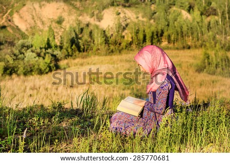 Muslim Woman Reading Holy Quran and praying outdoors - stock photo