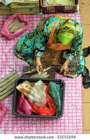 Muslim woman selling fresh vegetables at market in Kota Bharu Mal - stock photo