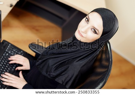 Muslim woman sitting on an office chair and working on the computer in the office. Overhead - stock photo