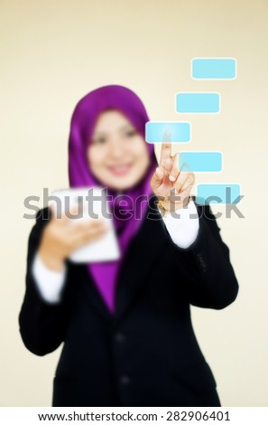 Muslim woman touching imaginary screen with her finger - stock photo