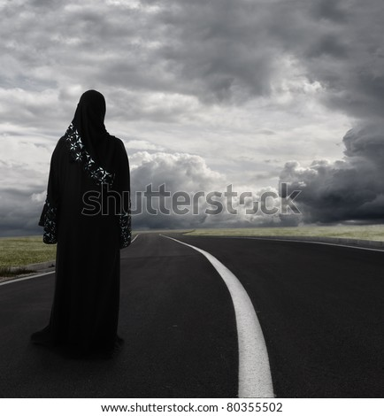 Muslim woman walking alone searching for the right path, conceptual image - stock photo