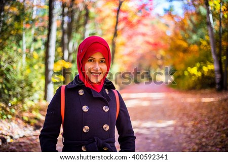 Muslim woman with colourful trees as background during autumn season  - stock photo