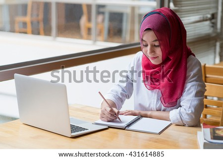 Muslim woman working with computer and writing notebook.