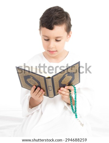 Muslim Young Boy Reading Quran And holding Rosary - stock photo