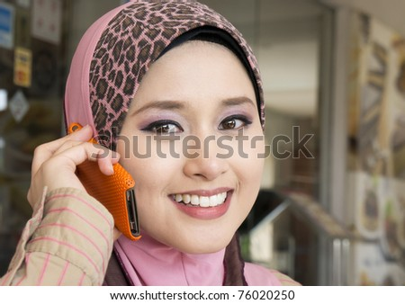 muslim young girl make a phone call - stock photo
