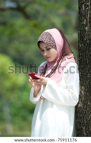 Muslim young woman in head scarf using phone in the park - stock photo