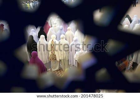 Muslimin and muslimat performing tarawih prayer at mosque during Ramadhan - stock photo