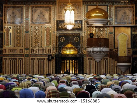 Muslims praying against a wall with Islamic patterns. - stock photo