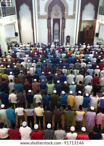 Muslims ready to perform Friday prayers lead by an imam (foreground, middle) in Kuala Lumpur, Malaysia. Male Muslims are compulsory to attend weekly Friday prayers. - stock photo