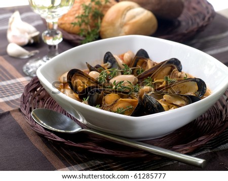 mussel soup with bean and thyme on bowl - stock photo