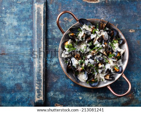 Mussels and Dor Blue sauce in copper cooking dish on blue background - stock photo
