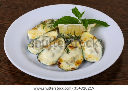 Mussels backed in cream sauce with rosemary on wood background - stock photo