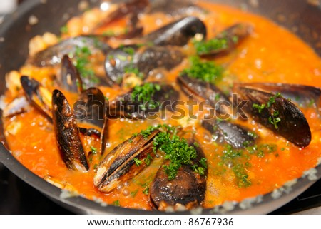 Mussels being cooked in tomato soup