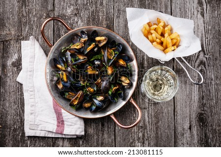 Mussels, french fries and wine on dark wooden background - stock photo