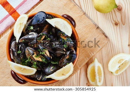 Mussels in a pot on the cutting board, lemons, tablecloth on wooden table - stock photo