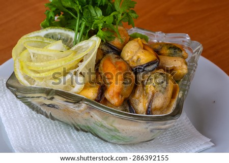 Mussels in butter sauce with lemon and parsley - stock photo