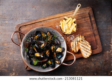 Mussels in copper cooking dish and french fries on dark wooden background - stock photo