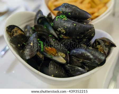 Mussels in White Wine and Garlic with Out of focus French fry and beer on the table. Mussels, cooked in white wine with aromatic herbs from Provence, French fries and a glass of beer