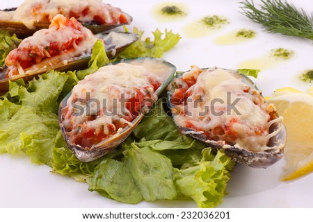 Mussels prepared with vegetables on a white dish close up - stock photo