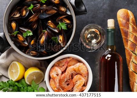 Mussels, shrimps and white wine on stone table. Top view - stock photo