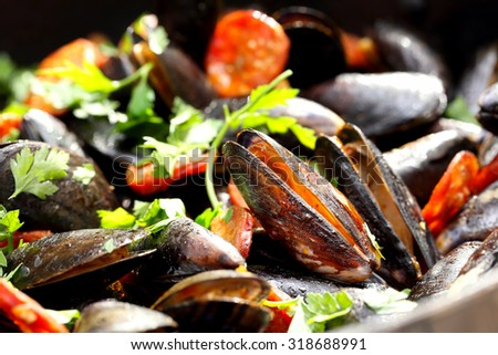 Mussels with chorizo and parsley in a pan