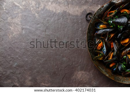 Mussels with parsley on stone slate background - stock photo