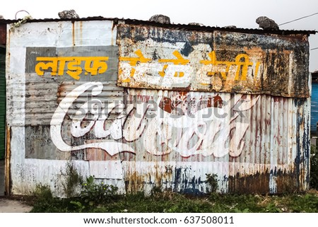 Mussoorie, India - March, 25th, 2015 Rusty, shabby wall with Pepsi and Coca-Cola hand painted advertisement