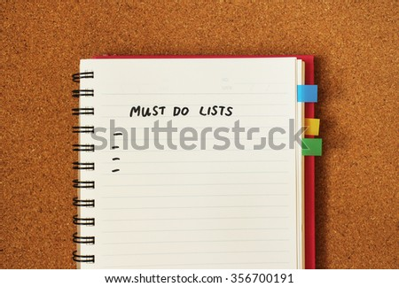 Must do list message in handwritten style with blank space to fill in the text. Blank page of notebook organizer with bookmark on cork board background.  - stock photo