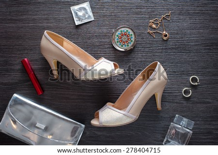Must have for party night. Overhead of essentials for modern young woman. Different objects on wooden background: silver handbag, condom, jewellery, heels and parfume. - stock photo
