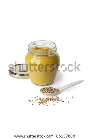 Mustard in a jar and mustard seeds on a spoon on white background - stock photo