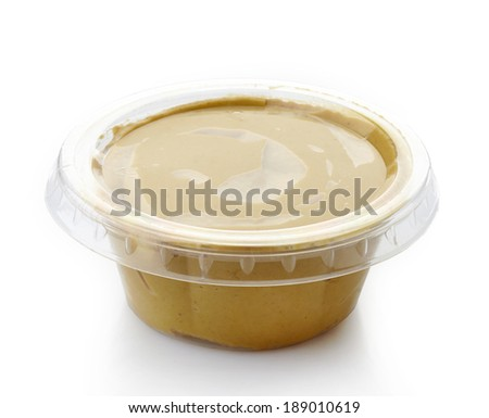 Mustard in a plastic take away container - stock photo