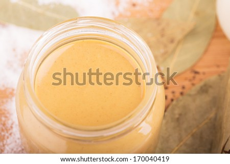 Mustard in a small glass jar close-up - stock photo