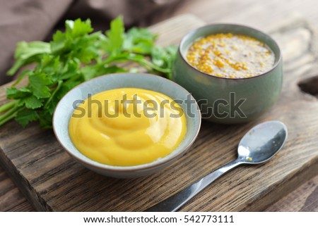 Mustard in the assortment: Dijon mustard and burning Russian mustard in bowls on wooden background
