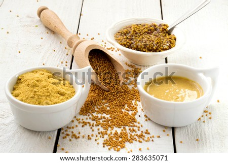 Mustard in the assortment: powder, grain in the wooden spoon, Dijon mustard, burning Russian mustard on a white wooden table. Selective focus - stock photo