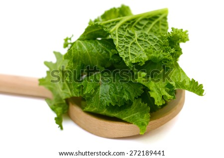 mustard salad slices on wooden spoon on white background  - stock photo