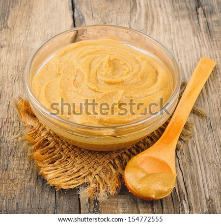 Mustard sauce in glass on wooden tables - stock photo
