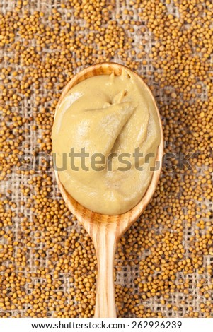 Mustard sauce in spoon with mustard seeds on vintage textile background - stock photo