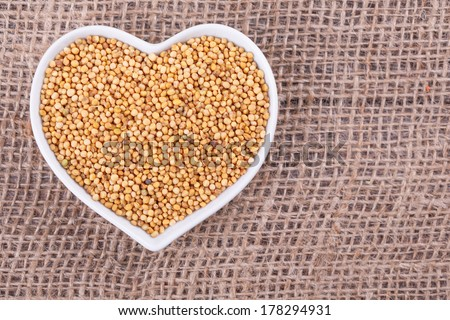 mustard seed in  cup in the shape of heart on sack  cloth - stock photo