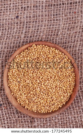mustard seeds in wooden cup  on  sack cloth - stock photo