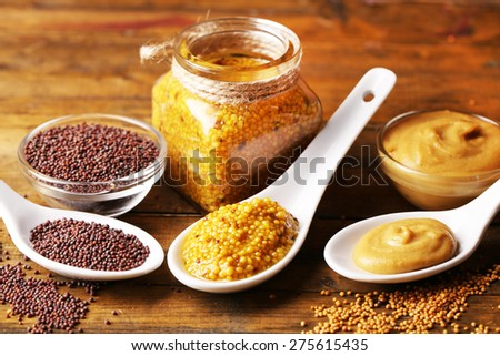 Mustard seeds, powder and sauce in spoons, bowls and glass jar on wooden background - stock photo
