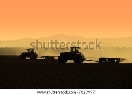 Muted Backlit Silhouette of Two Tractors Raking Soil - stock photo